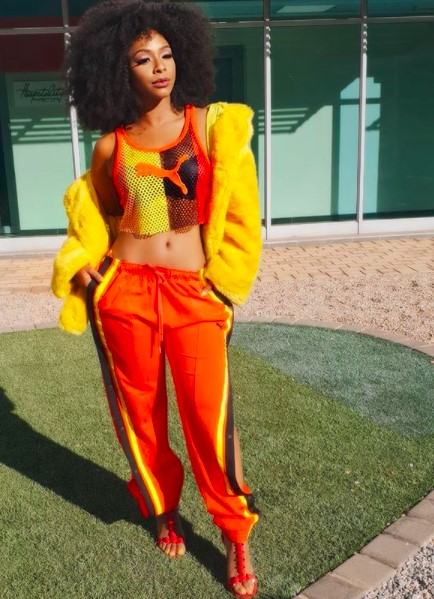 Boity wearing a costume and a curly weft