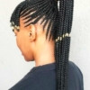 A person wearing a black shirt with beads as her hair accessories for braids