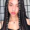 A person posing for the camera with hair ties braids accessories