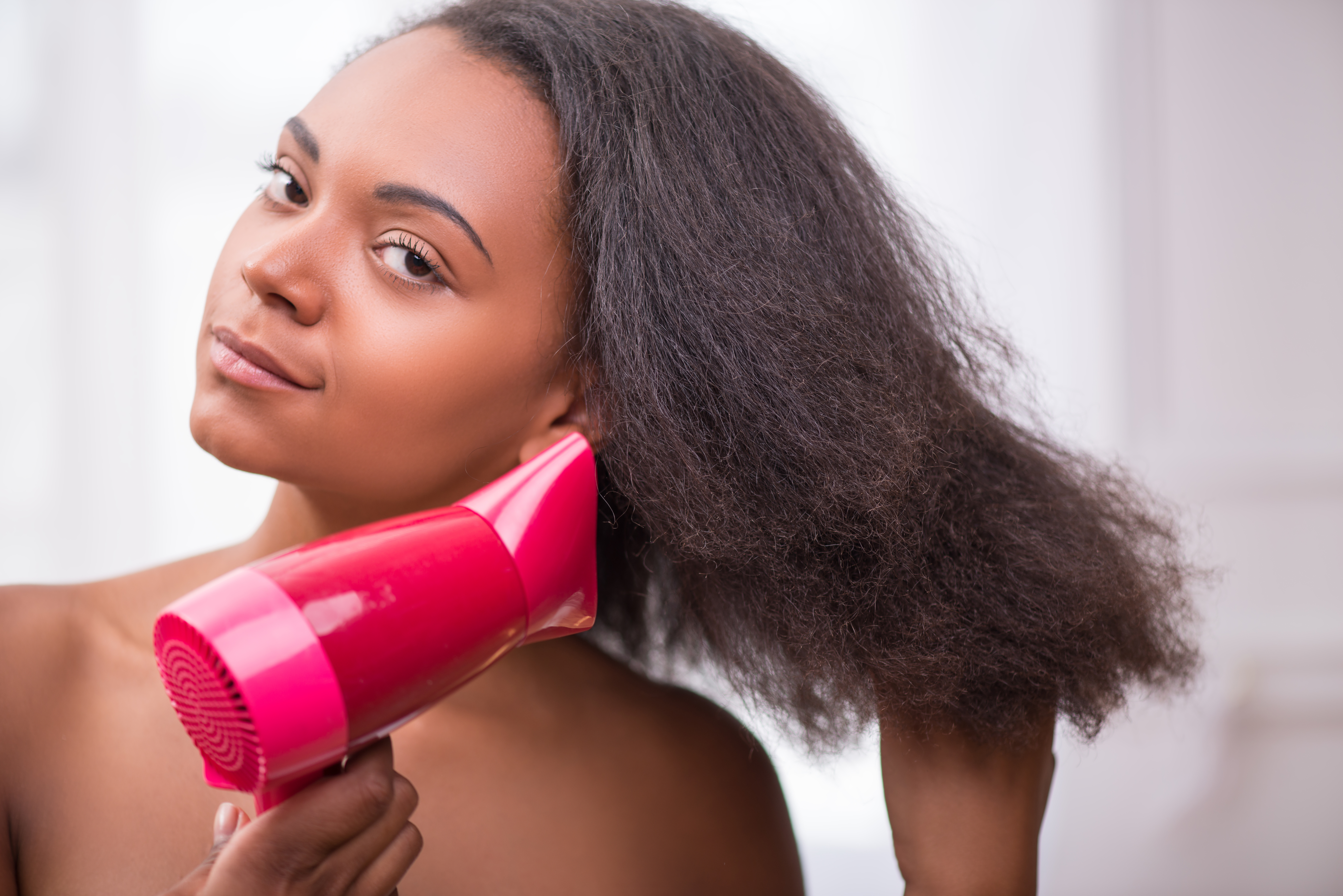 A person brushing her hair after applying hair moisturizer